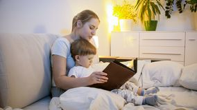 Portret van het mooie jonge verhaal van de moederlezing aan haar babyzoon royalty-vrije stock fotografie