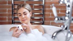 Portret van het mooie jonge vrouw genieten die gezichtsroom toepassen die bad middelgroot close-up nemen stock video