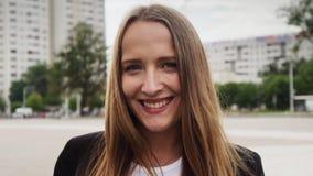 Portret van het mooie Kaukasische meisje glimlachen op de zomerdag in stad stock videobeelden