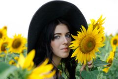 Portret van het mooie meisje met zonnebloemen Mooi zoet meisje in kleding en hoed die op een gebied van zonnebloemen lopen royalty-vrije stock afbeeldingen