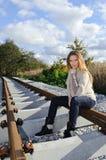 Portret van het mooie vrouw glimlachen en het zitten bij spoorwegen Royalty-vrije Stock Afbeeldingen