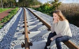 Portret van het mooie vrouw glimlachen en het zitten bij spoorwegen Stock Fotografie