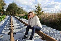 Portret van het mooie vrouw glimlachen en het zitten bij spoorwegen Royalty-vrije Stock Afbeelding