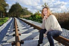 Portret van het mooie vrouw glimlachen en het zitten bij spoorwegen Stock Afbeelding