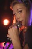 Portret van het mooie vrouwelijke zanger presteren in nachtclub stock afbeelding