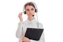 Portret van het nadenkende donkerbruine die meisje van de call centrearbeider met hoofdtelefoons en microfoon op witte achtergron Stock Fotografie