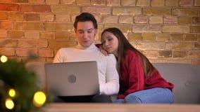 Portret van het ontspannen Kaukasische paar letten op in laptop en vrouw die op man s schouder op bank in huisatmosfeer liggen stock footage