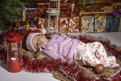 Portret van het pasgeboren babymeisje liggen onder deken naast Kerstboom en giftdozen stock foto's