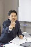 Portret van het punt van de zakenmanvinger in bureau Stock Foto's