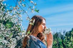 Portret van het ruiken van een boeket van bloemen jong meisje in kers g Stock Foto