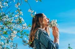 Portret van het ruiken van een boeket van bloemen jong meisje in kers g Stock Afbeelding