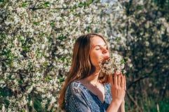 Portret van het ruiken van een boeket van bloemen jong meisje in kers g Stock Fotografie