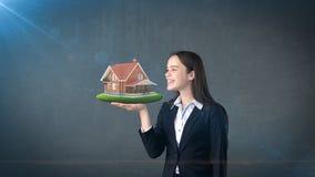 Portret van het rustieke blokhuis van de vrouwenholding op de open handpalm, over geïsoleerde studioachtergrond Bedrijfs concept Stock Foto's