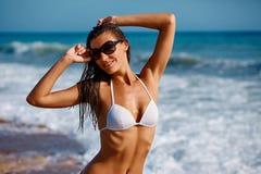 Portret van het sexy mooie gelooide vrouw stellen in kleurrijke swimwear bikini bij de van het overzeese reis en de rust kust Exo stock afbeeldingen