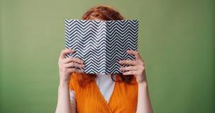 Portret van het slimme boek die van de tienerlezing dan camera en het glimlachen bekijken stock videobeelden