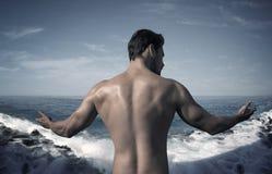 Portret van het spiermens stellen over de oceaan Stock Afbeelding