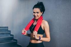 Portret van het sportieve gelukkige aantrekkelijke donkerbruine vrouw glimlachen met rode handdoek op hals na training in de gymn royalty-vrije stock afbeeldingen