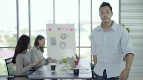 Portret van het succesvolle knappe Aziatische Belangrijkste creatieve zakenman glimlachen aan camera terwijl het werken in het bu stock videobeelden