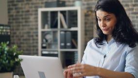 Portret van het vermoeide jonge dame typen met laptop en geeuw in werkplaats stock videobeelden
