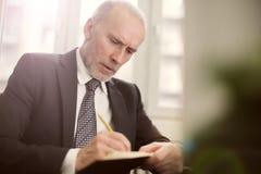 Portret van het volwassen zakenman schrijven stock foto's