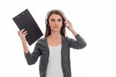 Portret van het vrij donkerbruine die meisje van de call centrearbeider met hoofdtelefoons en microfoon op witte achtergrond word Stock Foto's