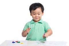 Portret van het vrolijke Aziatische jongen spelen met waterverf stock foto's
