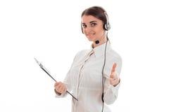 Portret van het vrolijke donkerbruine die meisje van de call centrearbeider met hoofdtelefoons en microfoon op witte achtergrond  Stock Foto's
