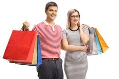 Portret van het vrolijke jonge paar stellen met het winkelen zakken stock afbeeldingen