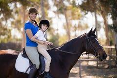 Portret van het Vrouwelijke jockey en meisjeszittingshorseback berijden stock afbeeldingen