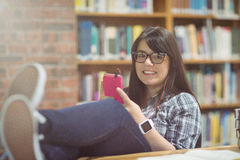 Portret van het vrouwelijke student luisteren aan muziek op mobiele telefoon Stock Afbeeldingen