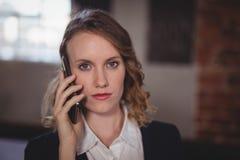 Portret van het zekere jonge mooie vrouwelijke redacteur spreken op cellphone Stock Fotografie