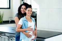 Portret van het zwangere lesbische paar omhelzen Stock Foto's