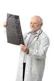 Portret van hogere arts die het beeld van de Röntgenstraal bekijkt Royalty-vrije Stock Afbeeldingen