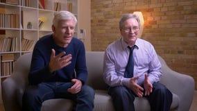 Portret van hogere mannelijke vrienden die op TV letten samen gelukkig en tevreden zijnd stock videobeelden