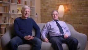 Portret van hogere mannelijke vrienden die samen op op TV letten en bank zitten die actief en vreugdevol bespreken stock footage