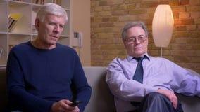 Portret van hogere mannelijke vrienden die samen op op TV letten en bank zitten die zijnd aandachtig en ernstig bespreken stock video
