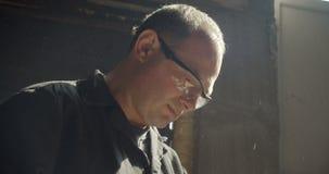 Portret van hogere timmerman in beschermende glazen die in en tevreden vervaardiging werken die worden geconcentreerd stock video