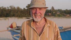 Portret van hogere visser in hoed dichtbij zijn vissersboot - Sicilië stock video
