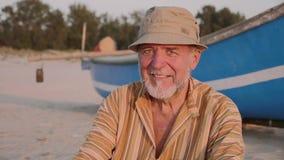 Portret van hogere visser in hoed dichtbij zijn vissersboot - Sicilië stock footage