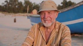 Portret van hogere visser in hoed dichtbij zijn vissersboot - Sicilië stock videobeelden
