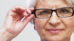 Portret van hogere vrouw die haar glazen aanpassen stock footage