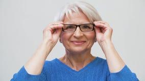 Portret van hogere vrouw die haar glazen aanzetten stock video