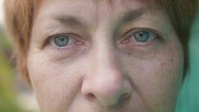 Portret van hogere vrouw op een groene achtergrond in de tuin stock videobeelden