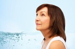 Portret van hogere vrouw over blauw water royalty-vrije stock foto