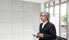 Portret van hogere zakenman in het bureau Hogere Aziatische busin stock afbeelding