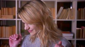 Portret van horloges de op middelbare leeftijd van de blondeleraar in camera die nadenkend en dromerig bij de bibliotheek zijn stock video