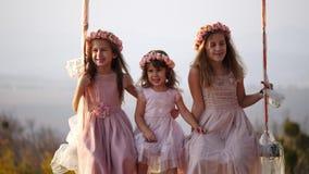 Portret van hree mooie meisjes die op een schommeling onder een grote boom slingeren stock videobeelden