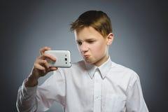 Portret van inbreukjongen met mobiele of celtelefoon Negatieve menselijke emotie stock fotografie