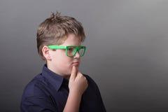 Portret van intelligent peinzend jong geitje met groene glazen Stock Foto