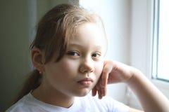 Portret van 12 jaar oud meisjes thuis dichtbij venster Stock Afbeelding
